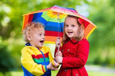 Little boy and girl play in rainy summer park. Children with colorful rainbow umbrella, waterproof jacket and coat playing in the rain. Kids walk in autumn shower. Outdoor fun by any weather.