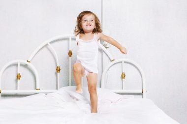 Active toddler girl dancing in bed
