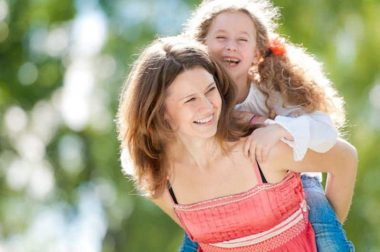 Beautiful and happy young mother giving piggyback ride to her laughing daughter